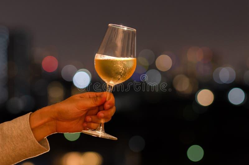 拿着一杯白酒的手敬酒对在屋顶酒吧的庆祝和党概念与城市光五颜六色的bokeh和 库存照片