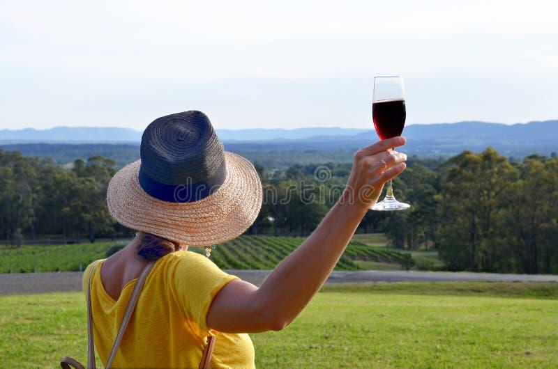拿着一杯红色汽酒,洪特尔谷,Ausralia的妇女 免版税图库摄影