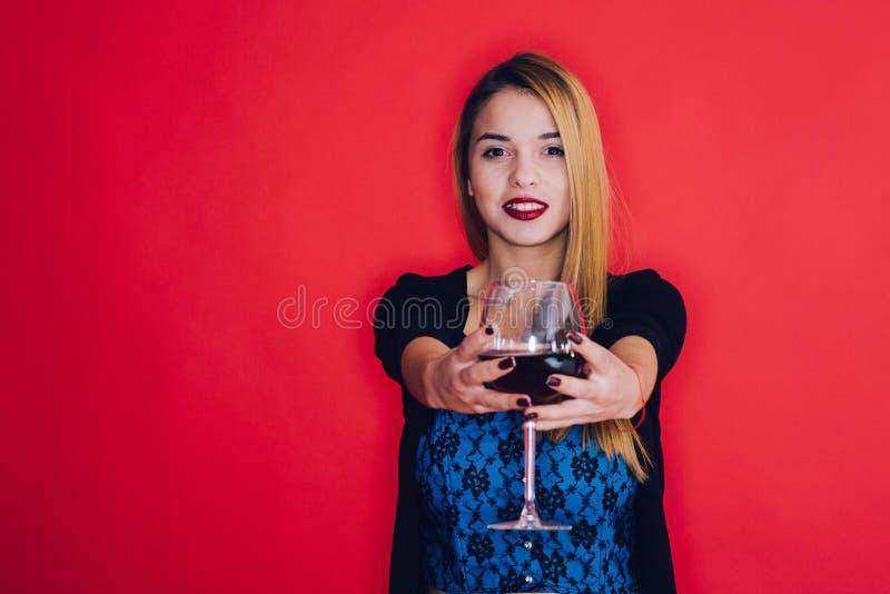拿着一杯红葡萄酒的女孩 免版税库存照片