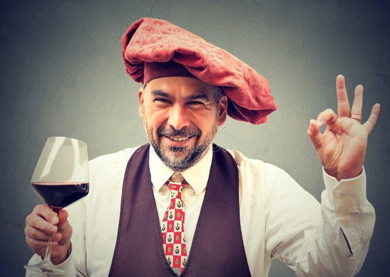 拿着一杯红葡萄酒的愉快的典雅的人 免版税图库摄影