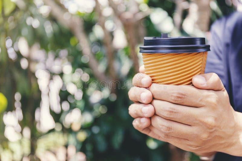拿着一杯纸咖啡的男性手特写镜头 免版税库存照片