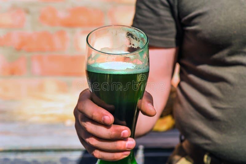 拿着一杯绿色啤酒的人 库存照片
