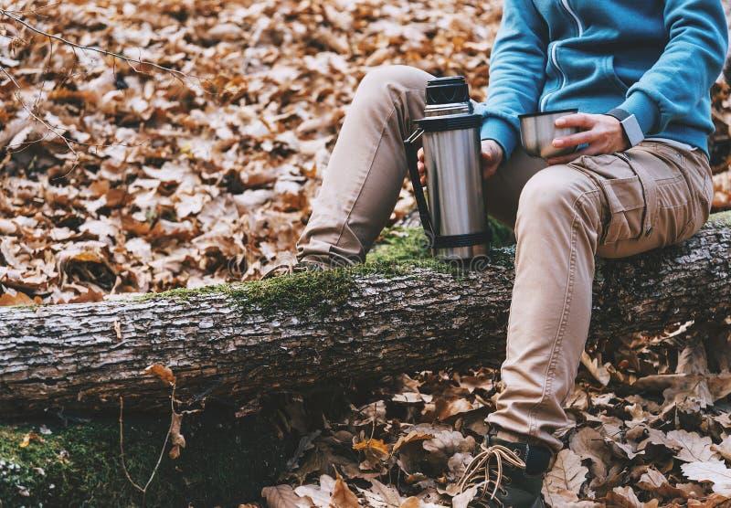 拿着一杯茶和热水瓶的远足者妇女在秋天森林里 库存照片