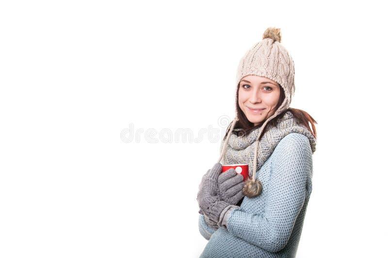 拿着一杯饮料的一件灰色T恤杉的可爱的少妇 背景查出的白色 库存图片