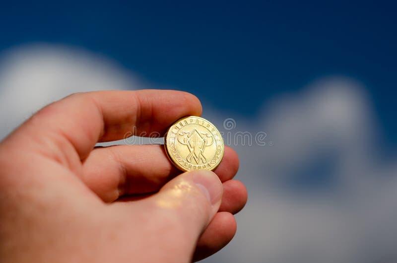 拿着一枚金黄硬币的手 库存图片
