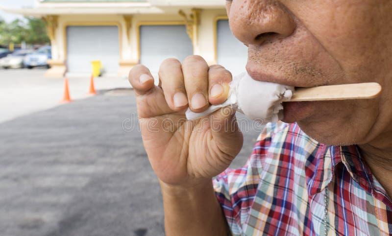 拿着一根木棍子的亚洲老人舔冰淇凌棍子 免版税图库摄影