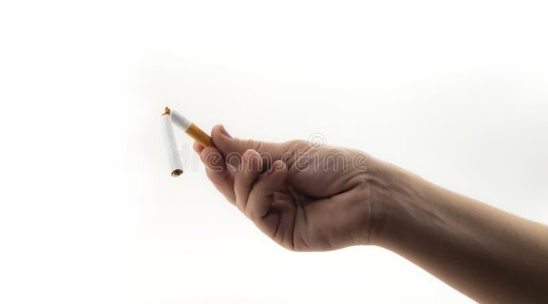 拿着一根残破的香烟的手由于被放弃的抽烟被隔绝在白色背景 免版税库存照片