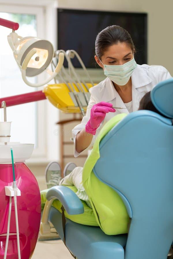 拿着一根牙齿探针的严肃的深色头发的妇女医生 免版税库存照片