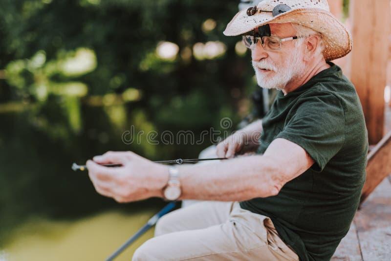 拿着一根钓鱼竿的宜人的有胡子的年迈的人 免版税库存照片