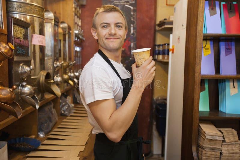 拿着一次性咖啡杯的男性推销员画象在商店 库存图片
