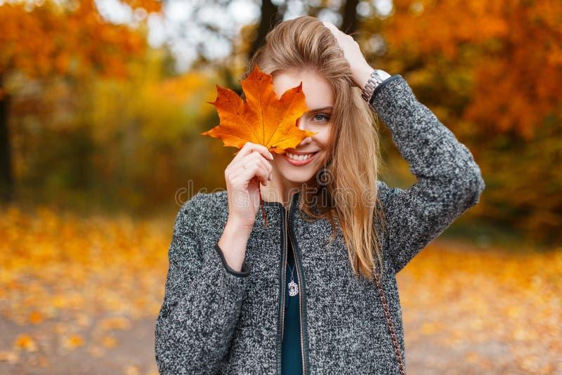 拿着一片明亮的黄色秋天叶子的一件时兴的灰色外套的美丽的年轻愉快的妇女在面孔附近在公园 快乐的女孩 库存图片