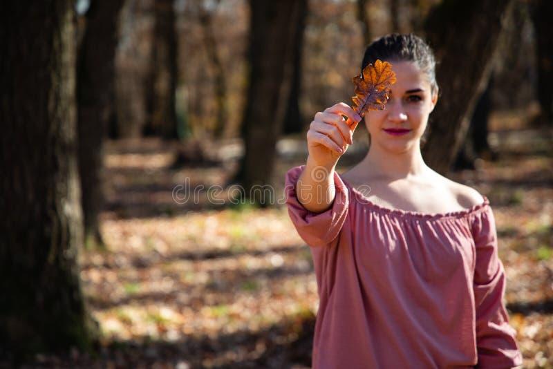 拿着一片棕色叶子的美女盖她的眼睛 免版税库存照片