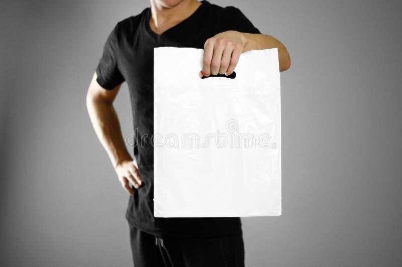 拿着一白色塑料袋的一个人 关闭 查出在灰色背景 库存照片