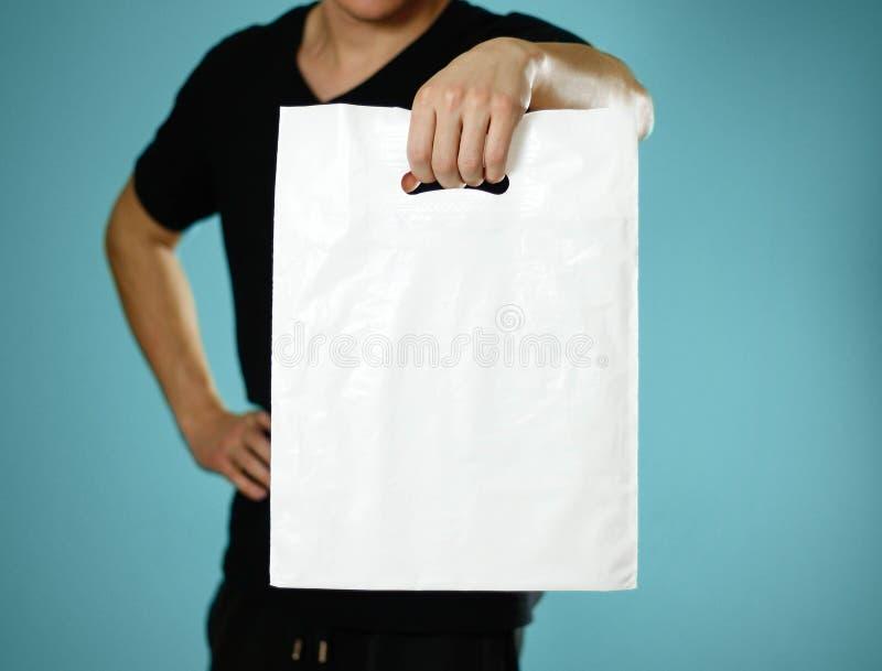 拿着一白色塑料袋的一个人 关闭 查出在蓝色背景 免版税图库摄影