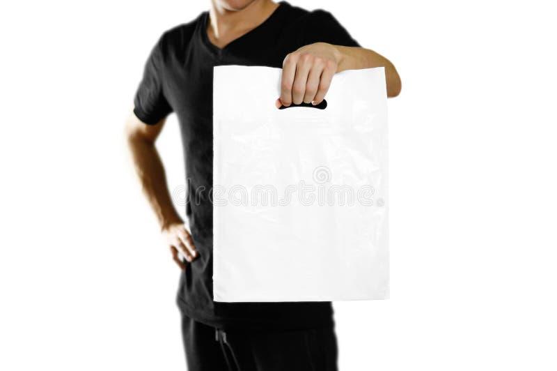 拿着一白色塑料袋的一个人 关闭 背景查出的白色 免版税库存照片