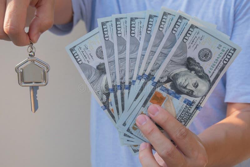 拿着一百元钞票和家庭形状钥匙链的亚裔人 物产投资和抵押财务概念 免版税库存照片