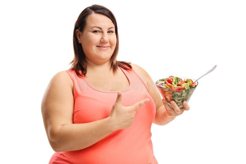拿着一碗新鲜的沙拉和指向它的胖的快乐的妇女 库存照片