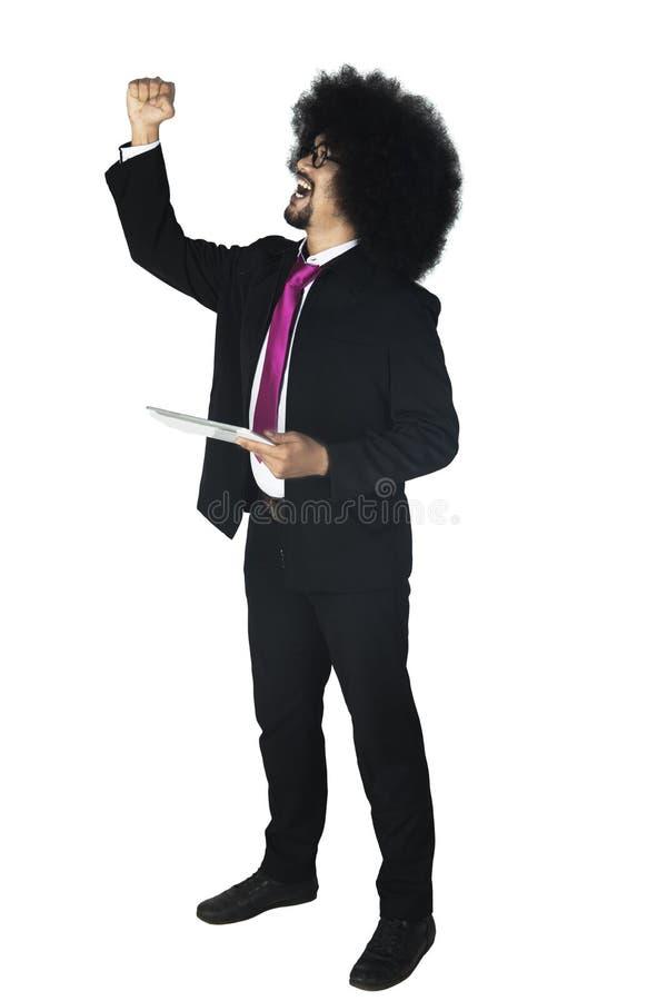 拿着一种数字式片剂的快乐的蓬松卷发商人 库存照片