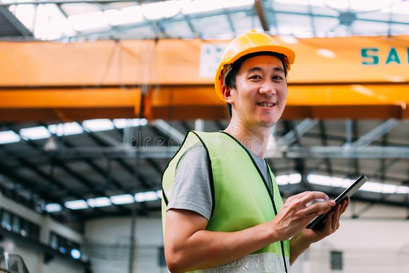 拿着一种数字片剂的年轻亚裔男性工厂劳工 免版税图库摄影