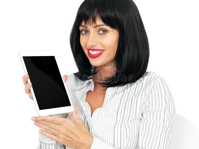拿着一种无线计算机片剂的可爱的少妇 免版税库存图片