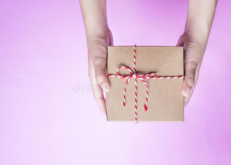 拿着一种简单的工艺的女性手裱糊被包裹的礼物盒 免版税库存照片