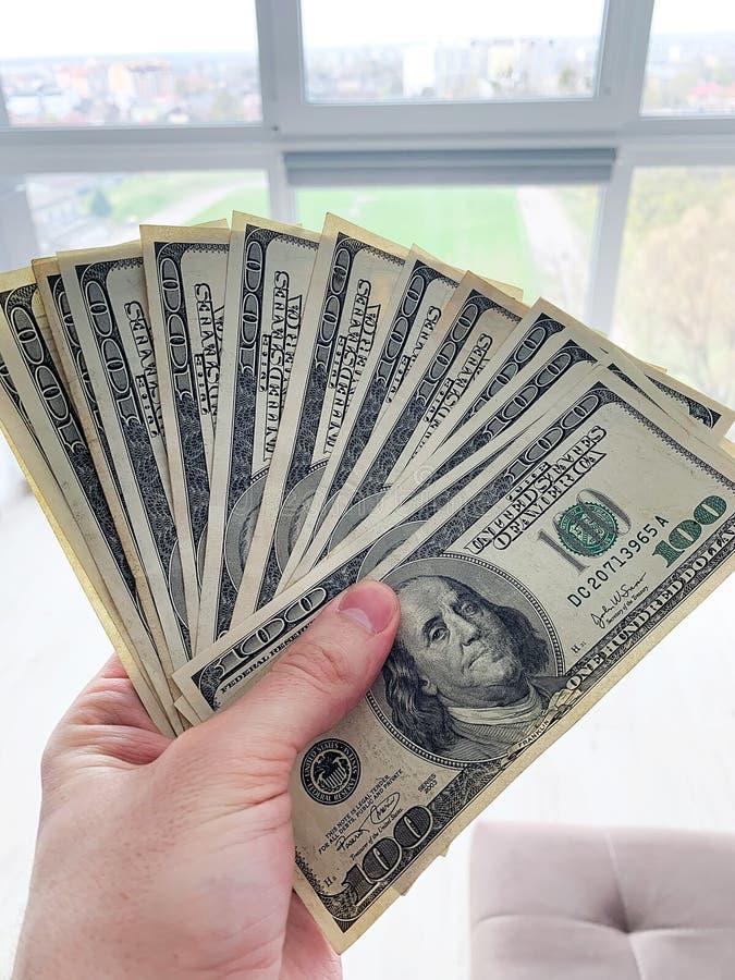 E 拿着一租务或购买舱内甲板的人一百美元钞票 免版税库存图片