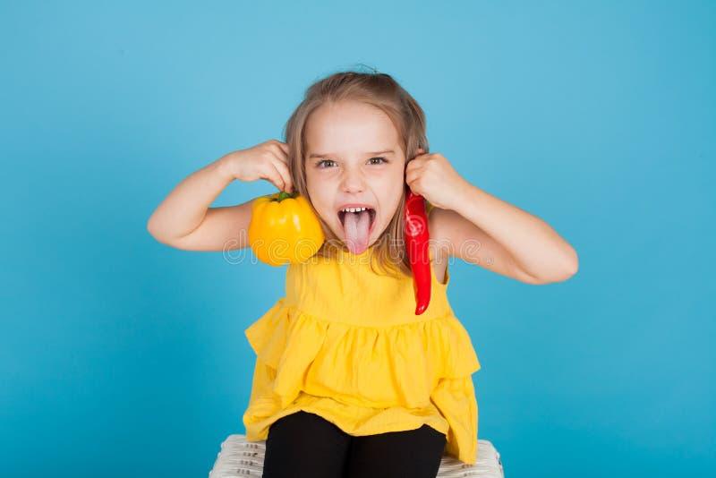 拿着一红色甜椒健康食品菜的女孩 免版税库存图片