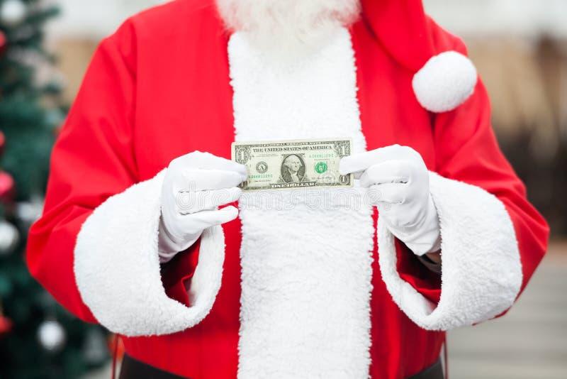 拿着一美元笔记的圣诞老人 免版税图库摄影