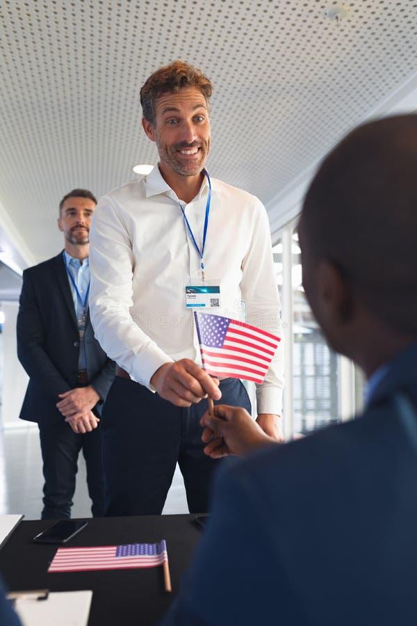 拿着一面美国国旗的商人在会议注册桌上 免版税库存照片