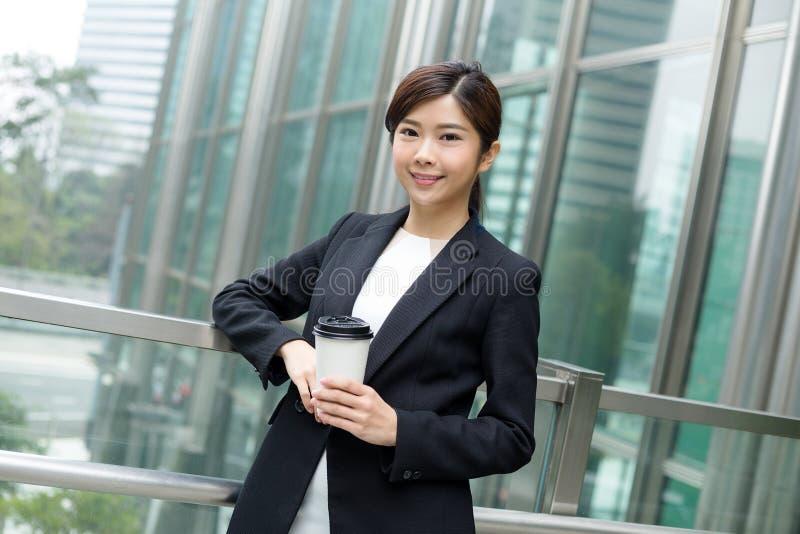 拿着一份咖啡在办公室外的女商人 免版税图库摄影