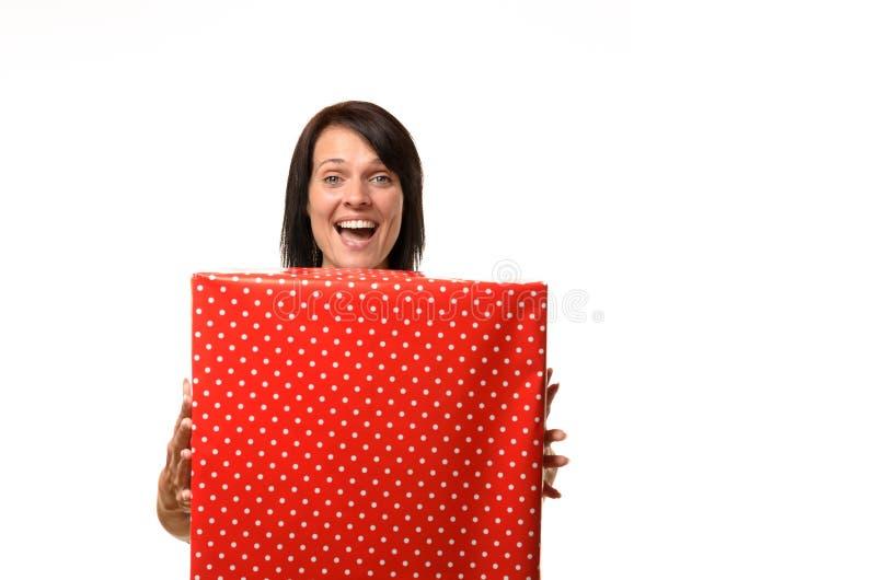拿着一件大红色礼物的愉快的极度高兴的妇女 免版税库存照片