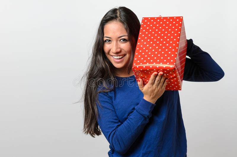 拿着一件红色礼物的激动的少妇 免版税库存照片