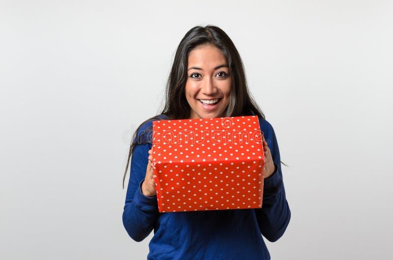 拿着一件红色礼物的激动的少妇 免版税图库摄影