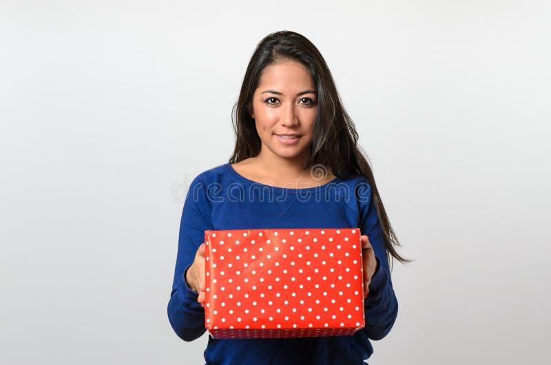 拿着一件红色礼物的激动的少妇 图库摄影
