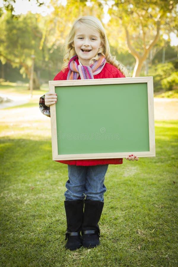 拿着一件绿色黑板佩带的外套的愉快的女孩 库存照片