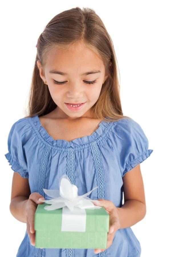 拿着一件被包裹的礼物的逗人喜爱的小女孩 库存图片