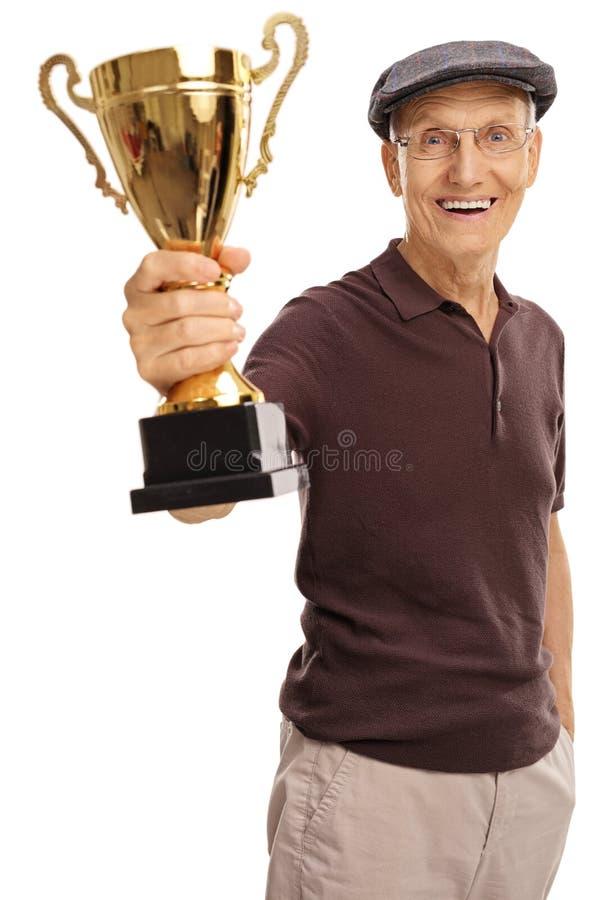 拿着一件金黄战利品的高兴年长人 库存图片