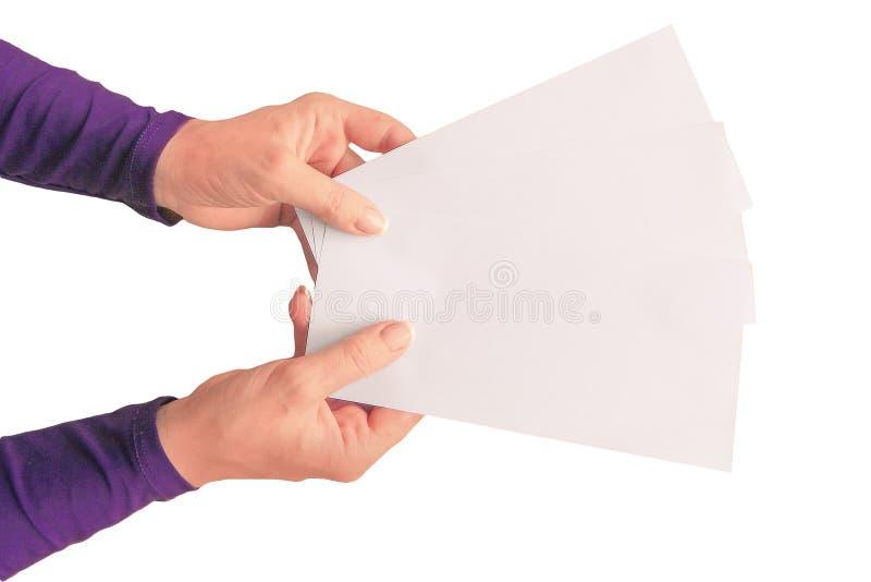 拿着三张白色纸的中间年迈的妇女的手 在被隔绝的背景的大模型 与拷贝空间的模板特写镜头 免版税库存照片
