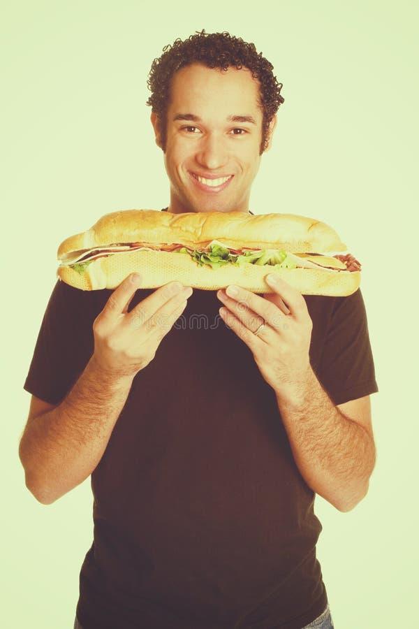 拿着三明治的人 免版税库存照片