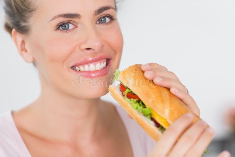 拿着三明治的快乐的妇女 图库摄影