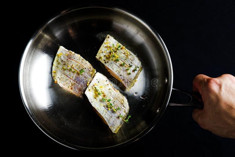 拿着三鱼片用草本和香料的手在平底锅 免版税图库摄影