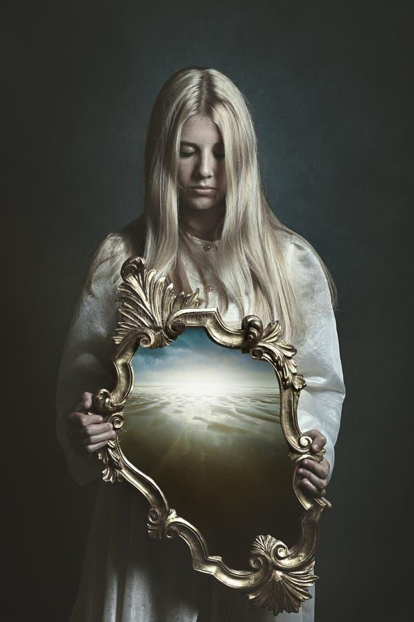 拿着不可思议的镜子的妇女 免版税库存照片