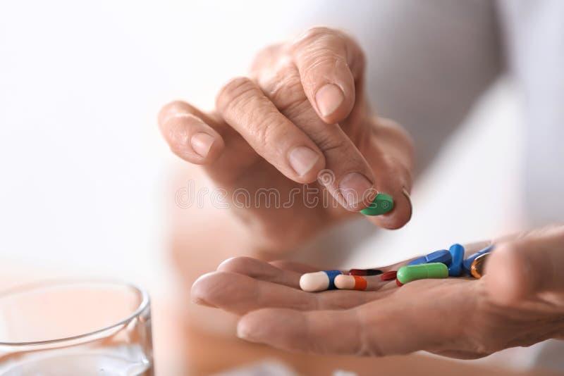拿着不同的药片,特写镜头的年长妇女 免版税库存图片