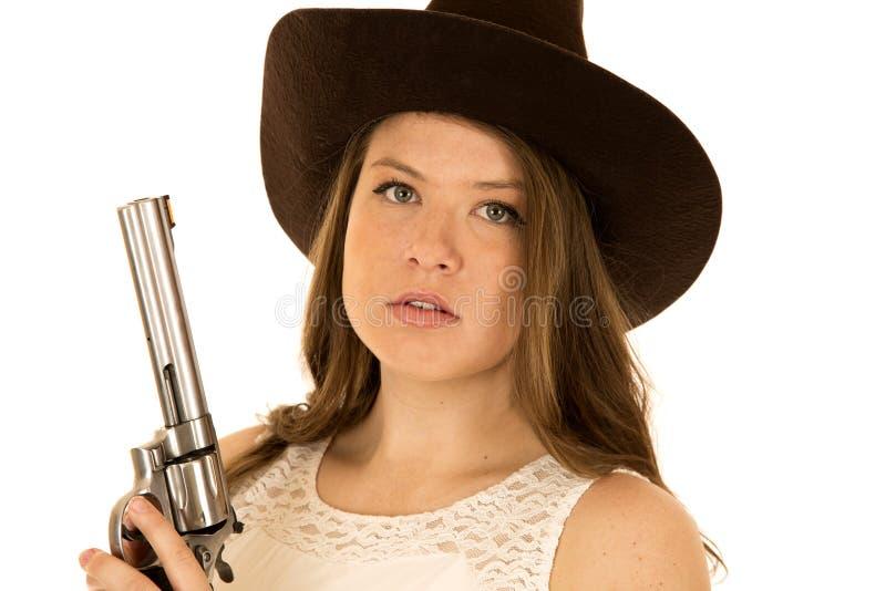 拿着与一个严肃的表示的女牛仔一把大左轮手枪 免版税库存照片
