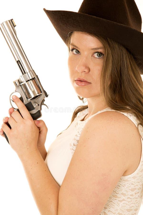 拿着与一个非常严肃的表示的女牛仔一把大左轮手枪 免版税库存图片