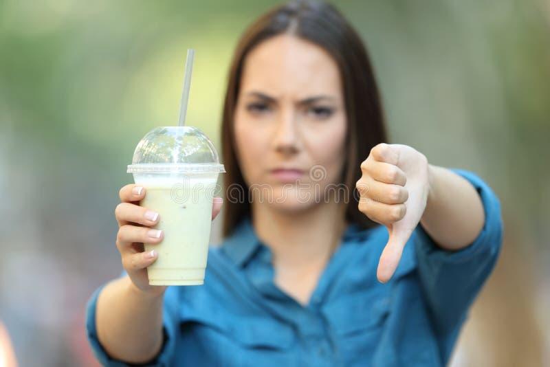 拿着与下来拇指的恼怒的妇女一名圆滑的人 图库摄影