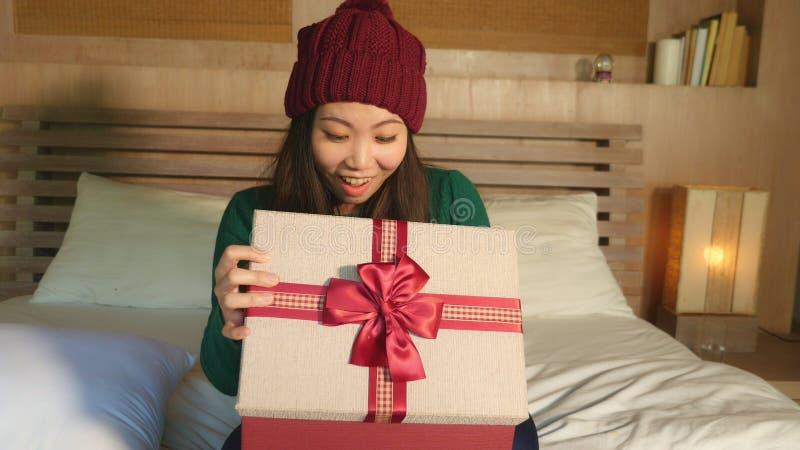拿着与丝带的冬天帽子的微笑年轻愉快的美丽的亚裔中国的女孩圣诞节giftbox激动和快乐的receivin 库存图片