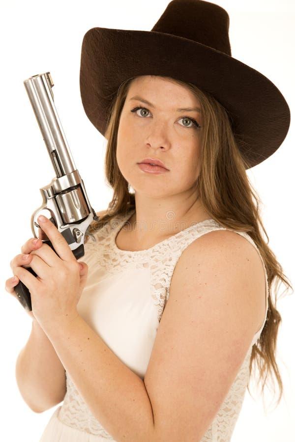 拿着与严肃表情看的女牛仔左轮手枪 库存图片