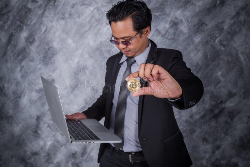 拿着与便携式计算机的商人金黄bitcoin 免版税库存照片