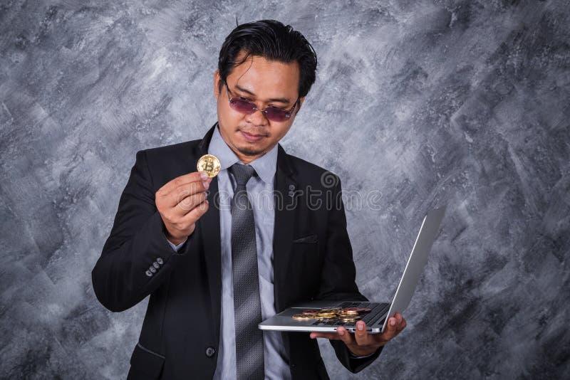 拿着与便携式计算机的商人金黄bitcoin 库存图片